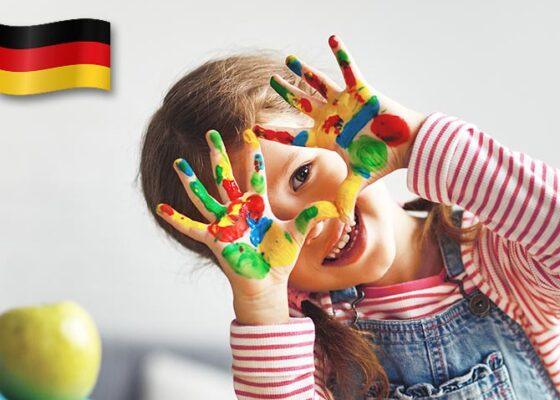 Fetiță, mâinile pline cu vopsea colorată