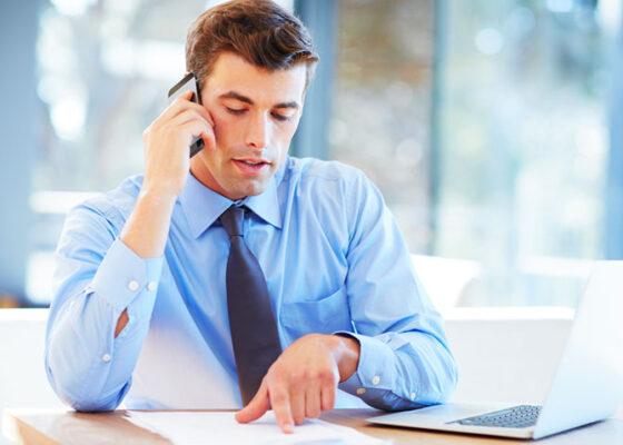 Bărbat atrăgător în cămașă și cravată care vorbește la telefon