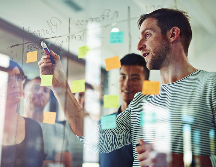Întâlnirea angajaților desenând o structură pe un panou transparent
