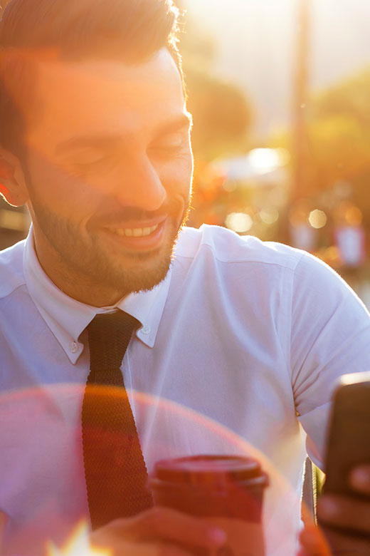 Tânăr în soare se uită la smartphone
